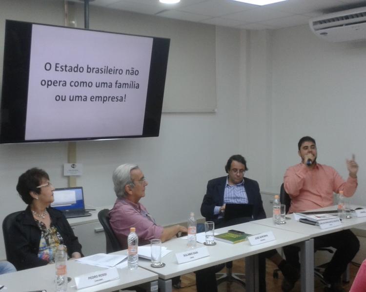 """Uma mulher e três homens em mesa de debates, tendo o da ponta direita falando ao microfone, assistido pelos demais; atrás e acima deles, um telão para apresentaões, onde se lê: ''o Estado brasileiro não opera como uma família ou uma empresa!"""""""