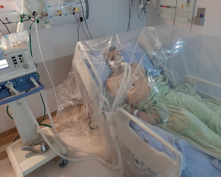 Quarto hospitalar, com equipamentos e cama hospitalar na qual um boneco, simulando um homem está deitado, sobre uma proteção plástica