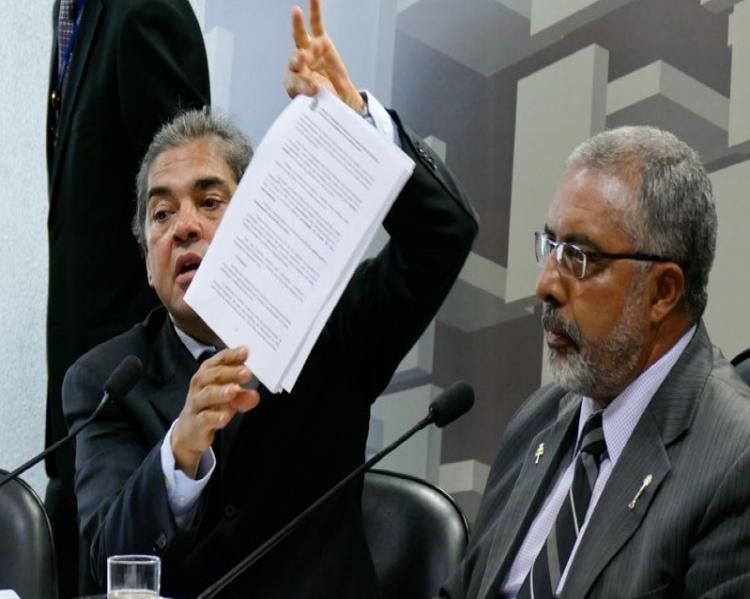 Homem à esquerda mostra uma folha de papel observado por um homem à direita. Ambos de ternos escuros.
