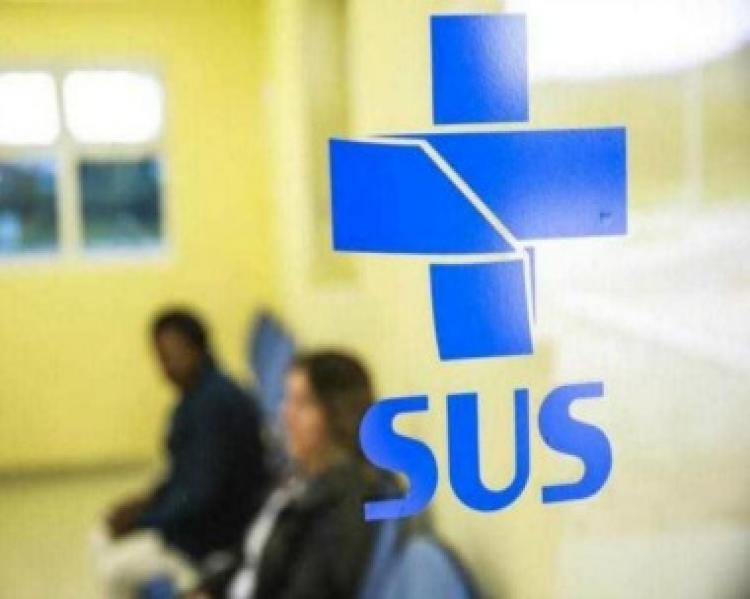 Vidro com a logomarca azul do SUS, mostrando atrás pessoas sentadas em espera