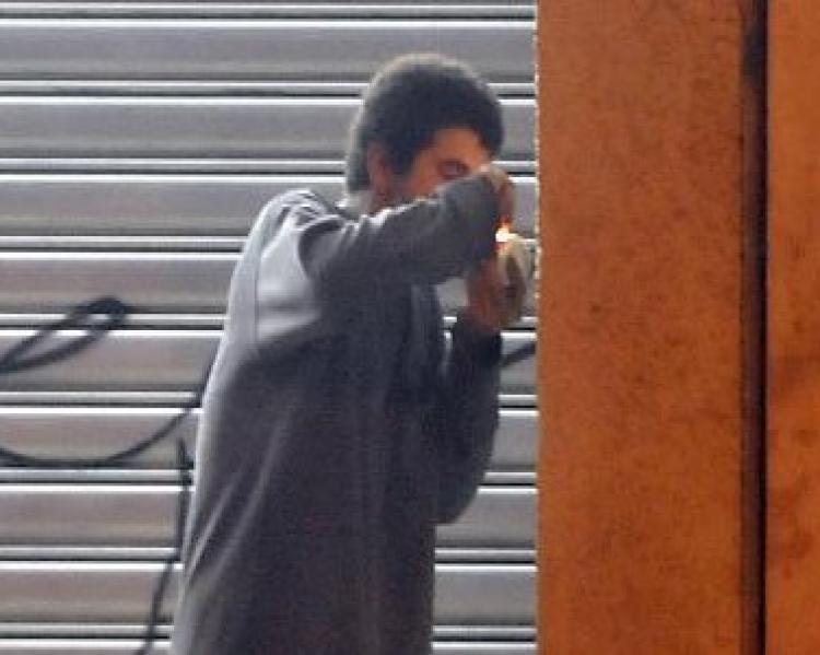 Homem de perfil, vestindo camiseta de manga comprida cinza, próximo a uma pilastra, usando crack