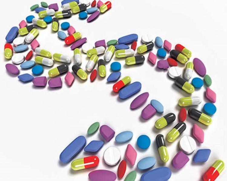 Cápsulas e comprimidos coloridos dispostos na forma de um cifrão