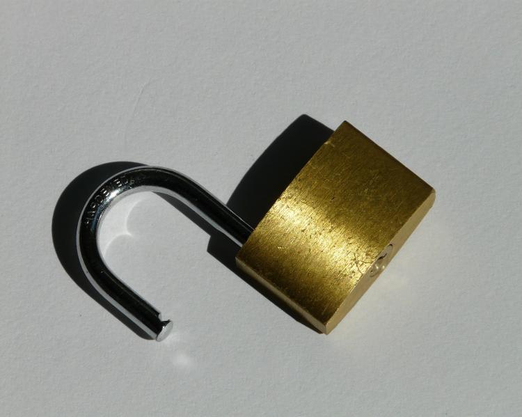 Cadeado prateado aberto sobre fundo cinza