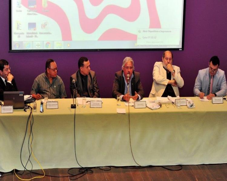 Seis homens em uma mesa de debates, um deles ao microfone