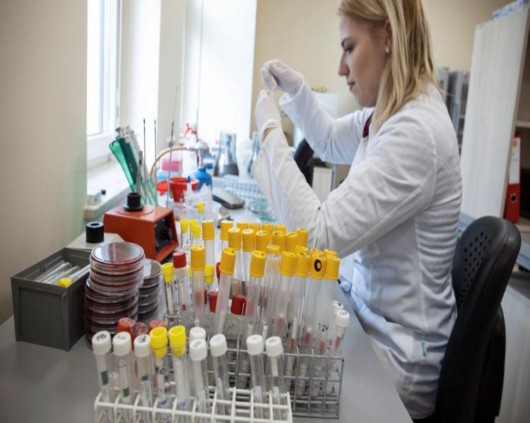 Mulher de jaleco branco manipula tubos ensaios sentada em uma bancada de laboratório
