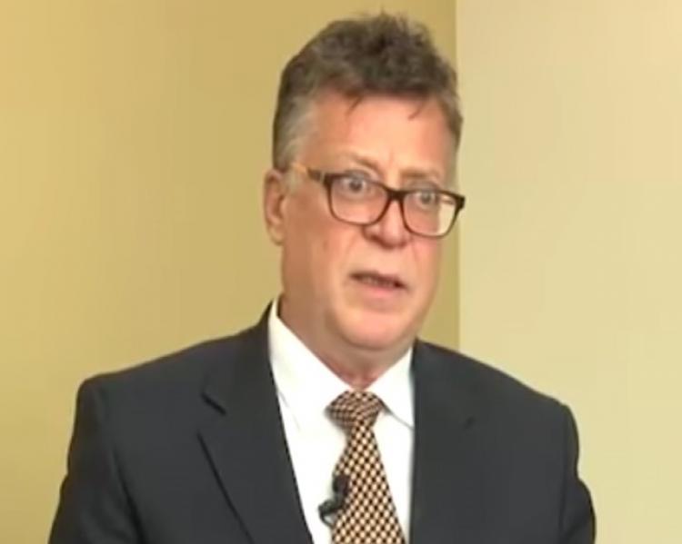 Homem de óculos e terno em close, com microfone na lapela