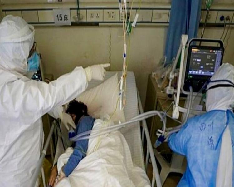 Profissionais de saúde com equipamentos de proteção observam paciente monitorizado em leito de UTI