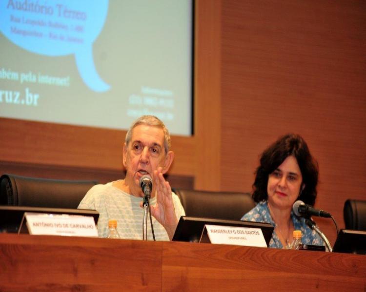 Wanderley Guilherme (homem grisalho em mesa de debate, gesticulando, ao lado de uma mulher de cabelos pretos, Nísia Trindade)