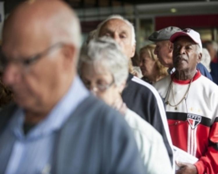 Fila com quatro idosos em primeiro plano, tendo na frente homem grisalho de óculos