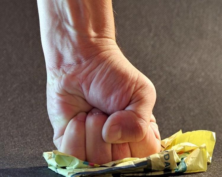 Mão fechada na vertical esmagando um papel amassado