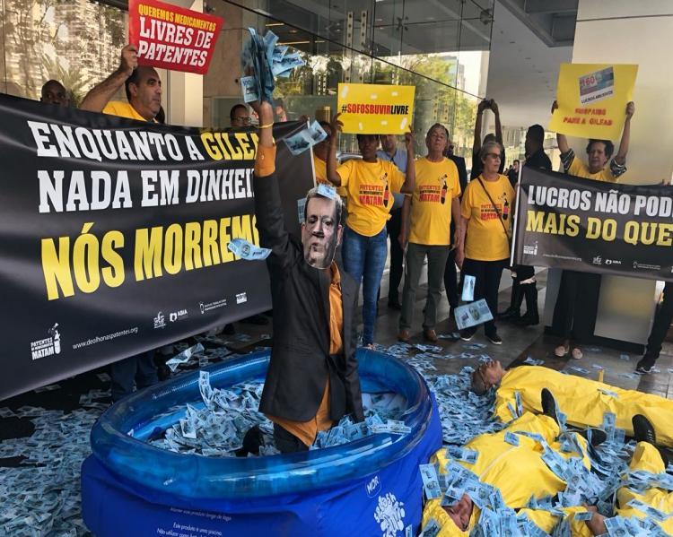 Homem dentro de uma piscina de plástico, com notas de dinheiro a sua volta e pelo chão, onde há pessoas deitadas; ao fundo, ativistas com cartazes contra patentes e com os dizeres 'Enquanto a Gilead nada em dinheiro, nós morremos'