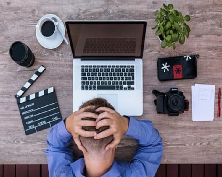 Homem de cabeça baixa com as mãos spbre a cabeça sentado a uma mesa com notebook, celular e outros equipamentos eletrônicos