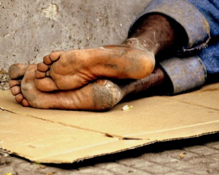 pés de morador de rua, deitado sobre um papelão