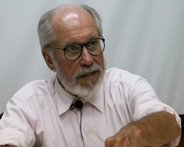 Homem grisalho de barba e óculos, de camisa clara, com microfone preso à lapela, fala e gesticula, sentado a uma mesa