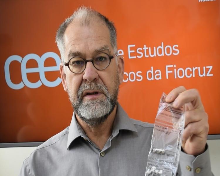 Homem de barba grisalha e óculos mostra uma tira plástica contendo comprimidos, em fundo laranja mostrando a logomarca do Centro de Estudos Estratégicos da Fiocruz