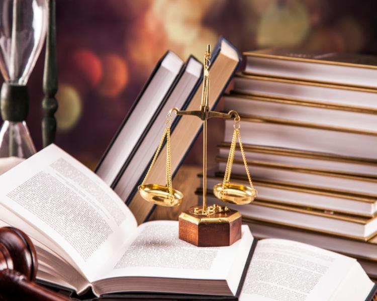 Livro aberto com uma pequena balança dourada sobre ele e uma pilha de livros ao fundo