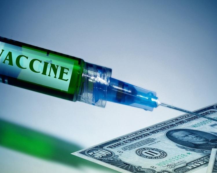 Seringa, onde se lê a palava 'vaccine' ligeiramente cortada,com a agulha apontadapara uma nota de dólar
