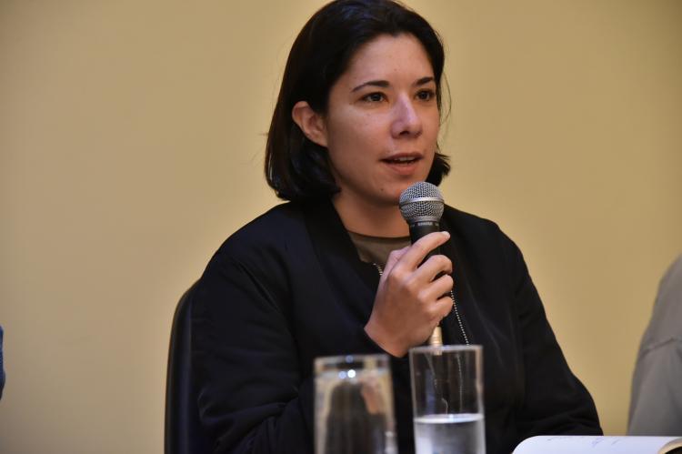 Mulher de cabelos pretos e casaco preto fala ao microfone