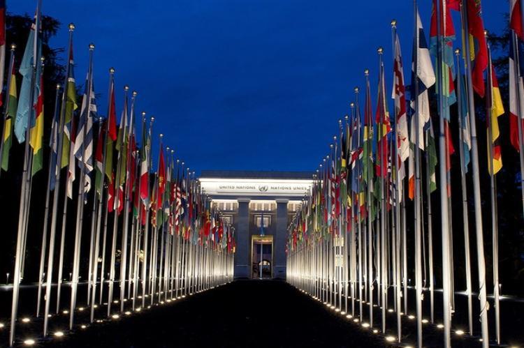 Duas fileiras de bandeiras de países, com a sede das Nações Unidas ao fundo, sob céu azul