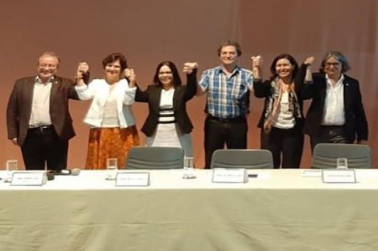 Homens e mulheres lado a lado erguem os braços de mãos dadas e sorriem