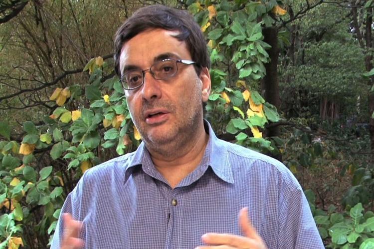 Homem em primeiro plano, de cabelos pretos curtos e óculos,  gesticula e fala