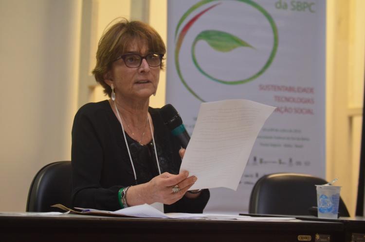 Mulher de óculos e cabelos curtos, de blusa preta segura sentada à mesa de debates segura um papel em uma das mãos e um microfone em outra