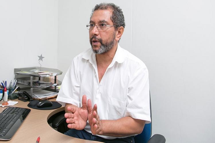 Rivaldo Venâncio (homem de barba, sentado à mesa de trabalho, com camisa branca, gesticulando