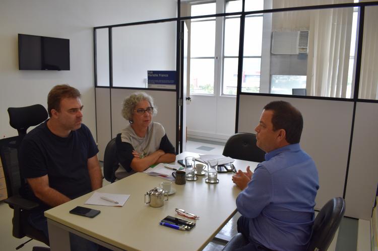 uma mulher e dois homens sentados a uma mesa retangular conversam