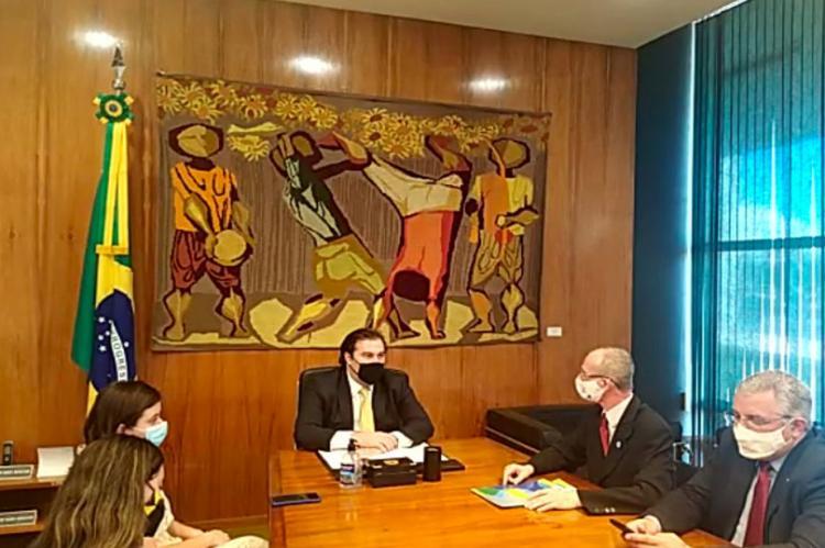 Homens de terno estão sentados em torno de uma mesa retangular tendo a bandeira do Brasil à esquerda