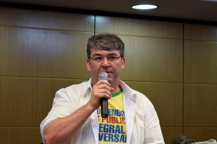 Ronald Santos (homem de óculos falando ao microfone, vestindo camisa sobre camiseta com dizeres em defesa da saúde