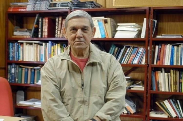 Wanderley Guilherme (homem em primeiro plano tendo atrás estante cheia de livros)