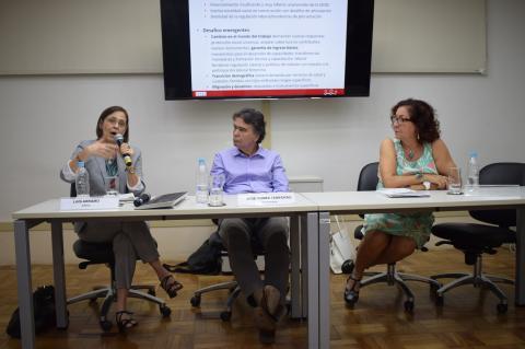 Três pessoas, duas mulheres e um homem ao centro, em uma mesa de debates, tendo-se ao fundo  um telão