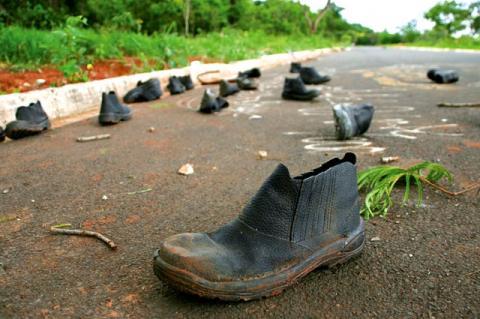 Botas pretas, abandonadas numa estrada