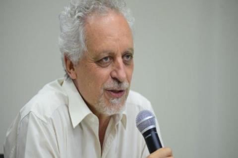 Homem grisalho, camisa branca, fala ao microfone