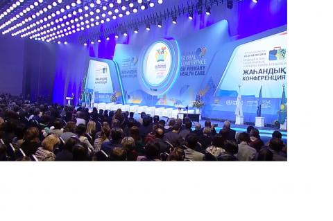 Plenária vista de cima, auditório lotado e grande mesa no palco, com projeção em lilás atrás, indicando o nome da conferência