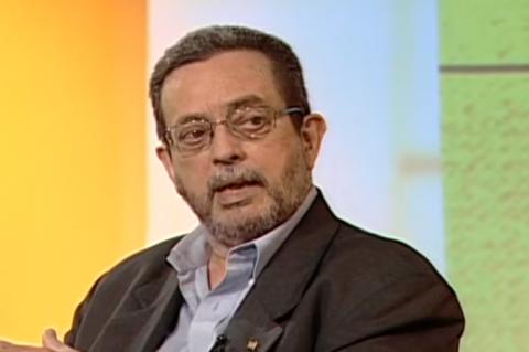 Homem de barba e óculos, vestindo paletó escuro, em fundo colorido