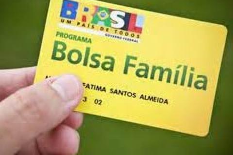 Mão segurando um cartão amarelo onde se lê Bolsa Família