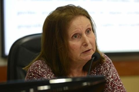 Mulher de cabelos claros e ongos de perfil em close, sentada em uma mesa de debates