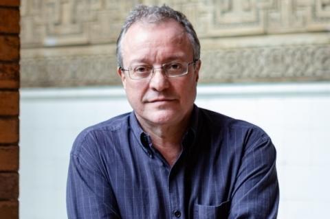 Homem de camisa social azul e óculos em primeiro plano