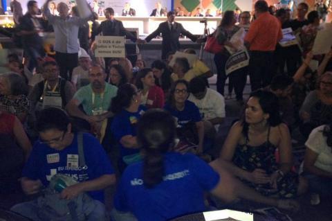 """De costas para o ministro da Saúde: cartazes dizem """"não ponham a mão no SUS""""; a cada palavra de Ricardo Barros, uma onda de vaias e manifestações de repúdio (Foto: Adelante – Coletivo Saúde e Democracia)"""