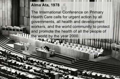foto antiga em preto e branco mostra uma plenária vista do alto, com um palco à frente e pessoas na mesa de debates