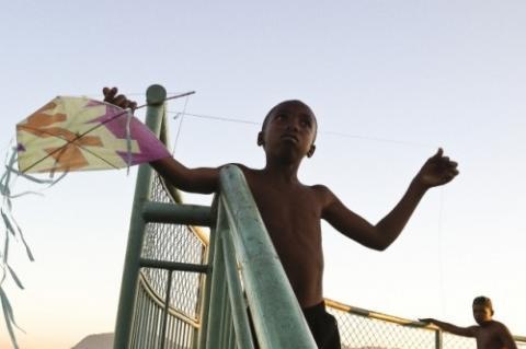 Menino sem camisa, no alto de uma escada segura uma pipa