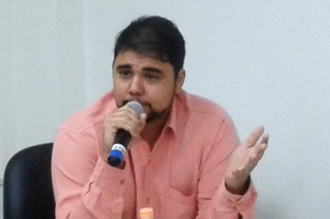 Homem de cabelos pretos curtos e barba gesticula falando ao microfone