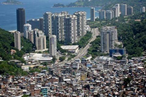 Favela em primeiro plano e prédios altos próximos ao mar, ao fundo