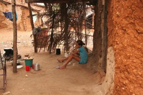 Criança ao longe sentada no chão de terra, na porta de casa