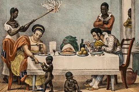Quadro mostrando cena doméstica do século 19, com duas pessoas negras em pé, a mulher abanando pessoas brancas sentadas a uma mesa e crianças negras sem roupa brincando no chão
