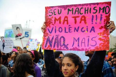 Mulher mostra cartaz com fundo rosa, onde se lê: seu machismo mata! Seu machismo não mais!