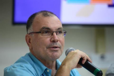 Homem em primeiro plano, de óculos e camisa azul, ao microfone