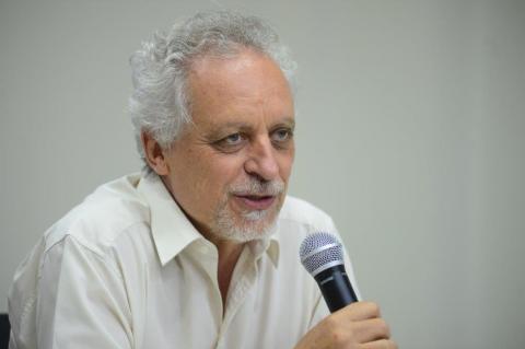 Homem grisalho de camisa branca fala ao microfone