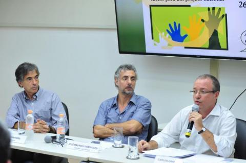 Luis Fernandes, José Maurício Domingues e Carlos Gadelha (três hons sentados em uma mesa de debates, o da ponta direitaao microfone e os demais observando)